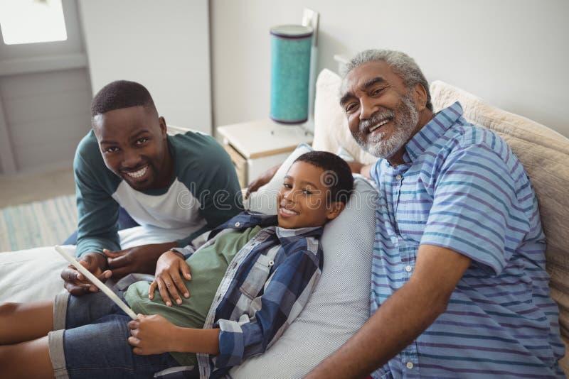 família da Multi-geração que usa a tabuleta digital na cama imagem de stock royalty free