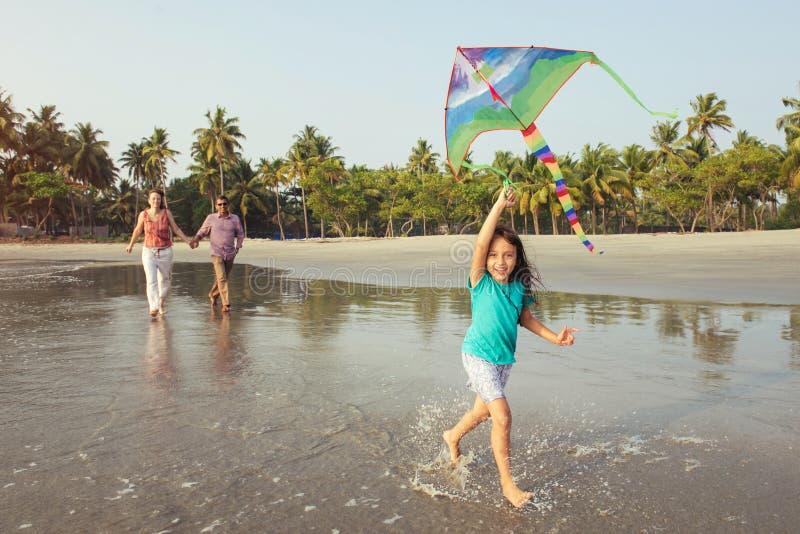 Família da raça misturada que anda com a criança no mar no por do sol imagens de stock royalty free