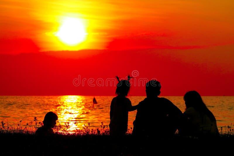família da silhueta no céu borrado praia do por do sol fotografia de stock