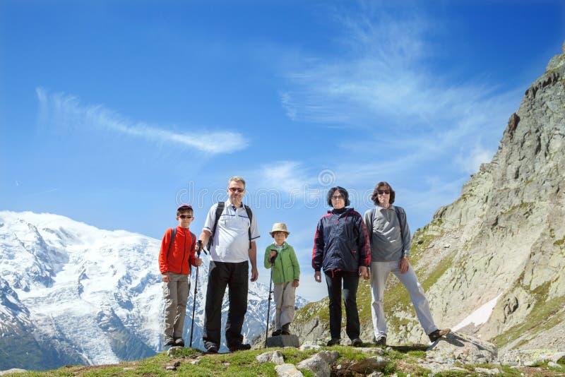 A família de cinco pessoas fica contra o maciço de Mont Blanc imagem de stock royalty free
