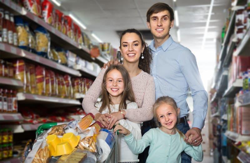 Família de pais novos e duas de crianças que fazem a compra fotografia de stock
