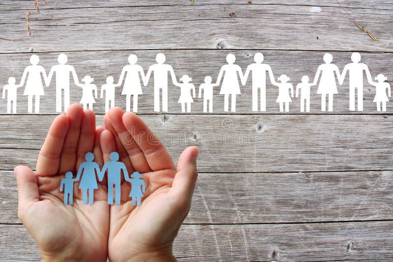 Família de papel nas mãos no fundo de madeira com famílias brancas imagens de stock