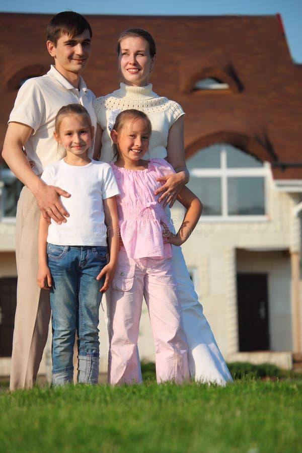 Família de quatro carrinhos na grama de encontro à casa foto de stock
