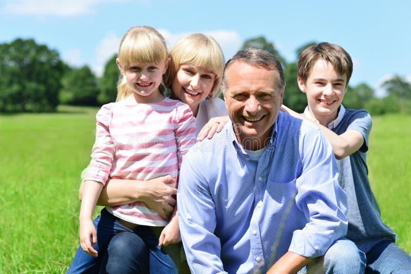Família de quatro pessoas alegre em um dia ensolarado brilhante imagem de stock royalty free