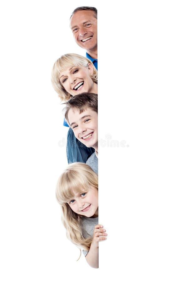 Família de quatro pessoas atrás do whiteboard vazio imagem de stock royalty free