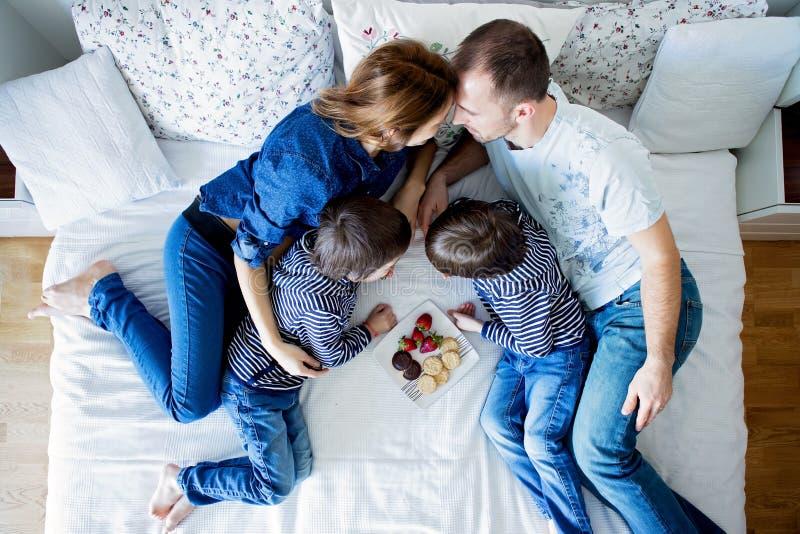 Família de quatro pessoas bonita, encontrando-se na cama, comendo morangos imagens de stock