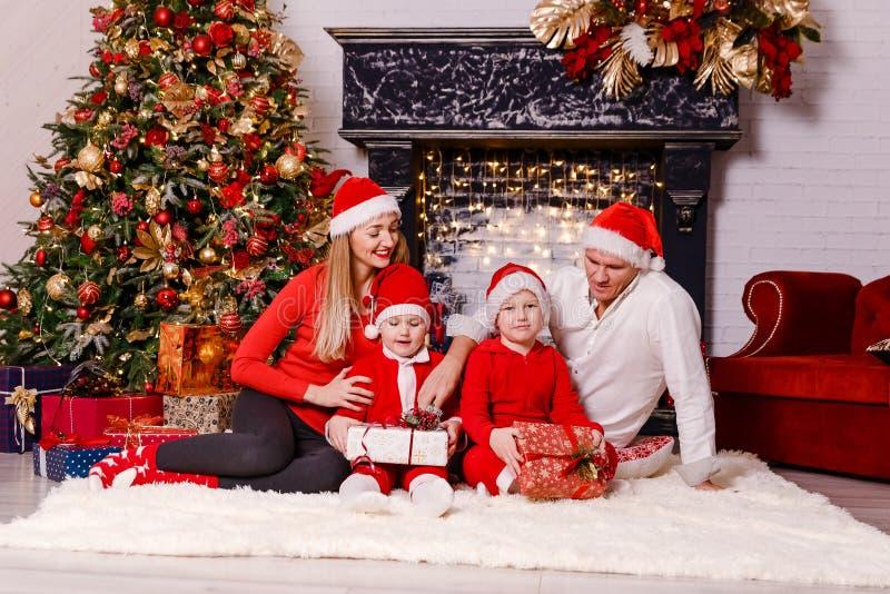 Família de quatro pessoas bonita que senta-se em uma cobertura macia na sala do Natal foto de stock royalty free