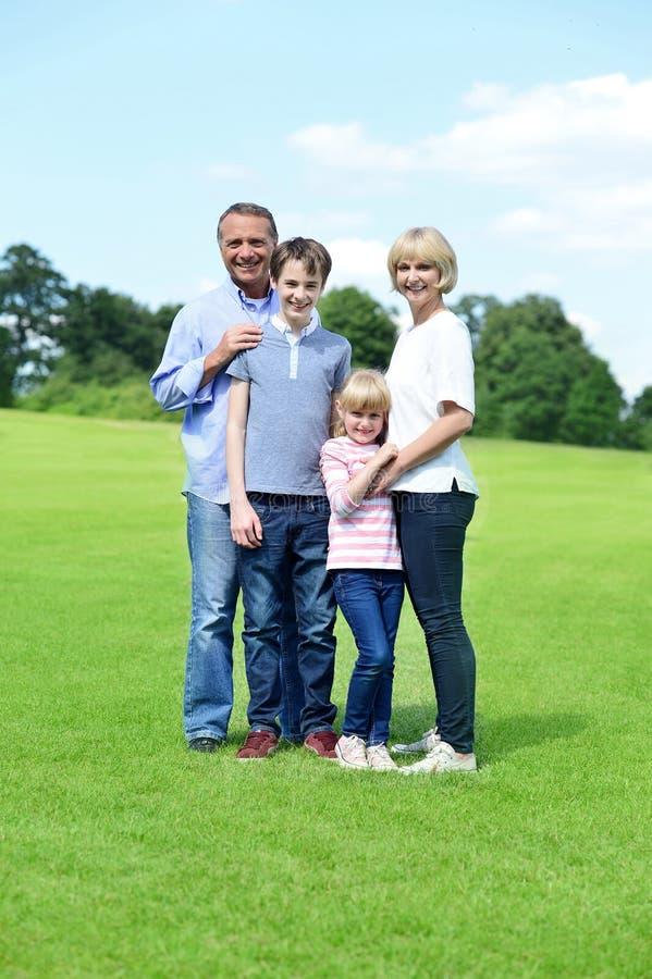 Família de quatro pessoas bonito que levanta à câmera foto de stock