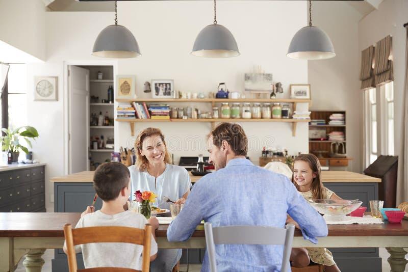Família de quatro pessoas branca que tem o almoço em sua cozinha em casa fotos de stock royalty free