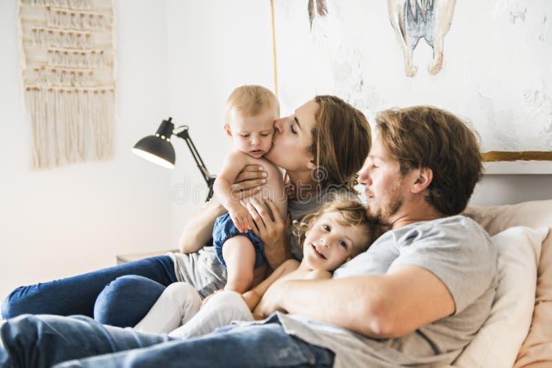 Família de quatro pessoas com o bebê que tem o divertimento na cama imagens de stock royalty free