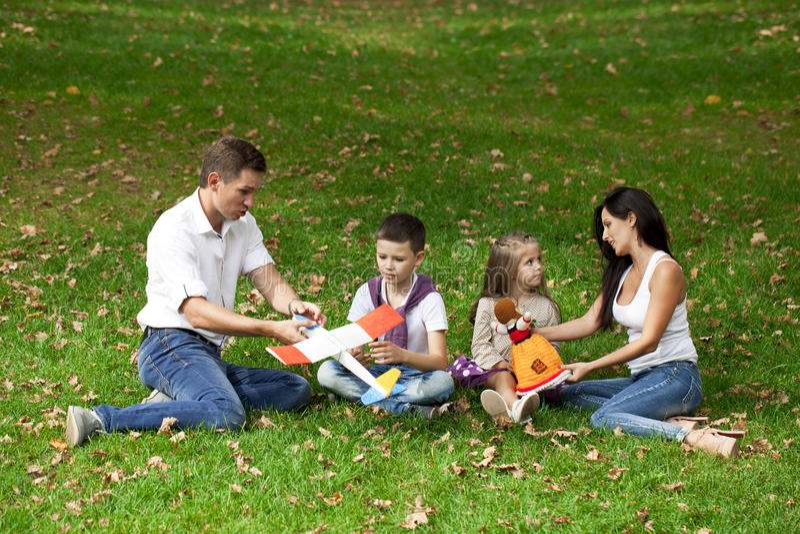 Família de quatro pessoas feliz, descansando no parque do outono imagens de stock royalty free