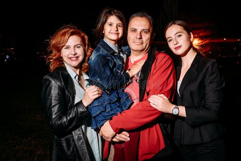 Família de quatro pessoas feliz na noite contra um fundo escuro fotografia de stock royalty free