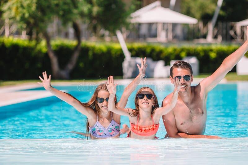 Família de quatro pessoas feliz na piscina do ar livre fotos de stock royalty free