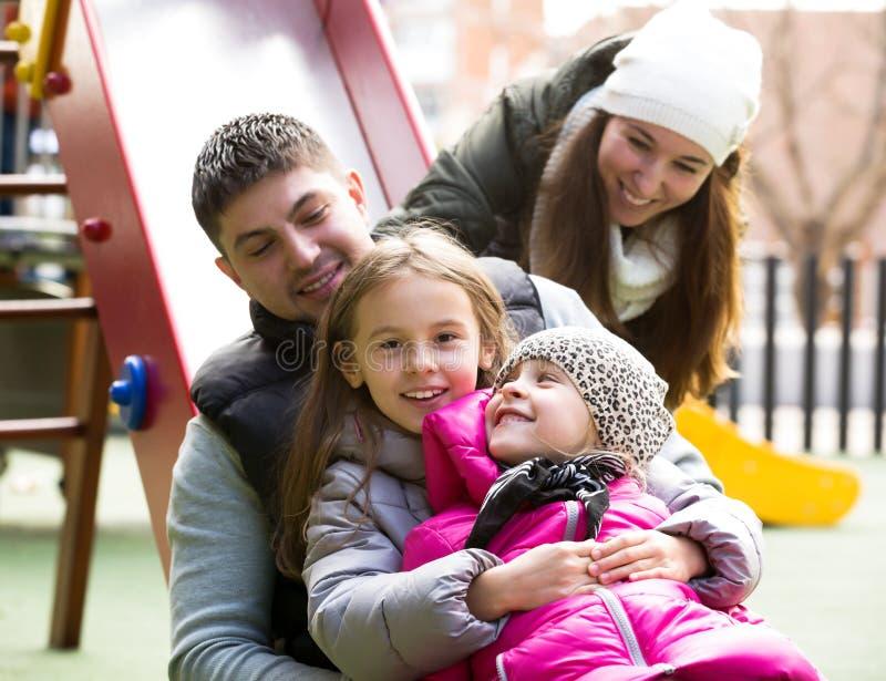 Família de quatro pessoas feliz no children& x27; campo de jogos de s fotografia de stock