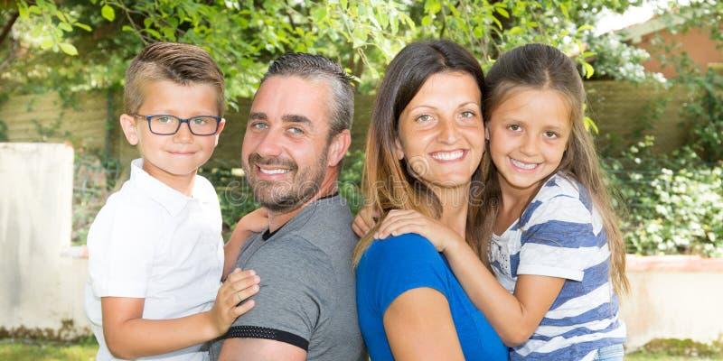 Família de quatro pessoas feliz no parque do jardim do campo fotos de stock