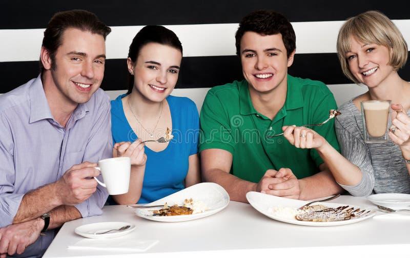 Família de quatro pessoas feliz no restaurante imagem de stock royalty free