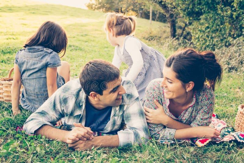 Família de quatro pessoas feliz que encontra-se na grama no outono fotografia de stock royalty free