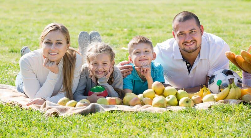 Família de quatro pessoas feliz que encontra-se no parque fotos de stock royalty free