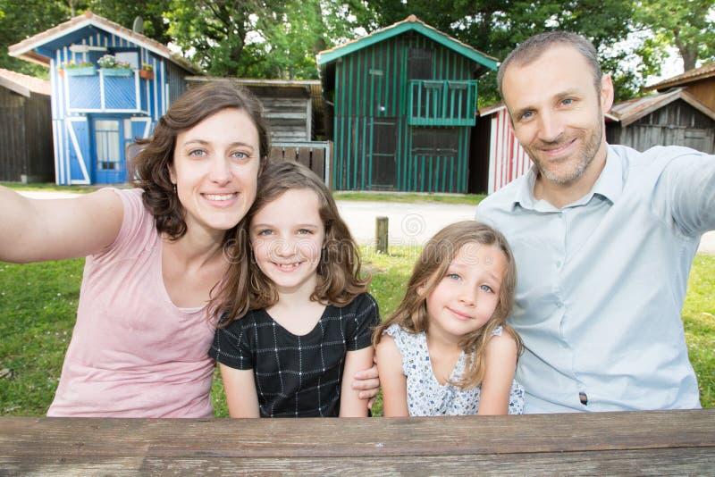a família de quatro pessoas feliz que faz o selfie fora gena a mãe e a filha que levantam em Biganos Bassin Arcachon em França fotos de stock
