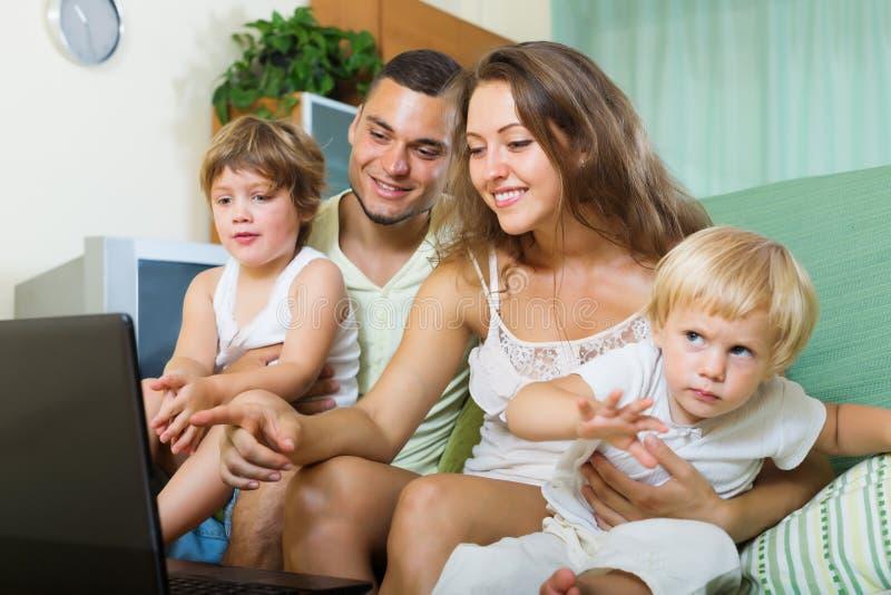 Família de quatro pessoas feliz que olha o portátil foto de stock
