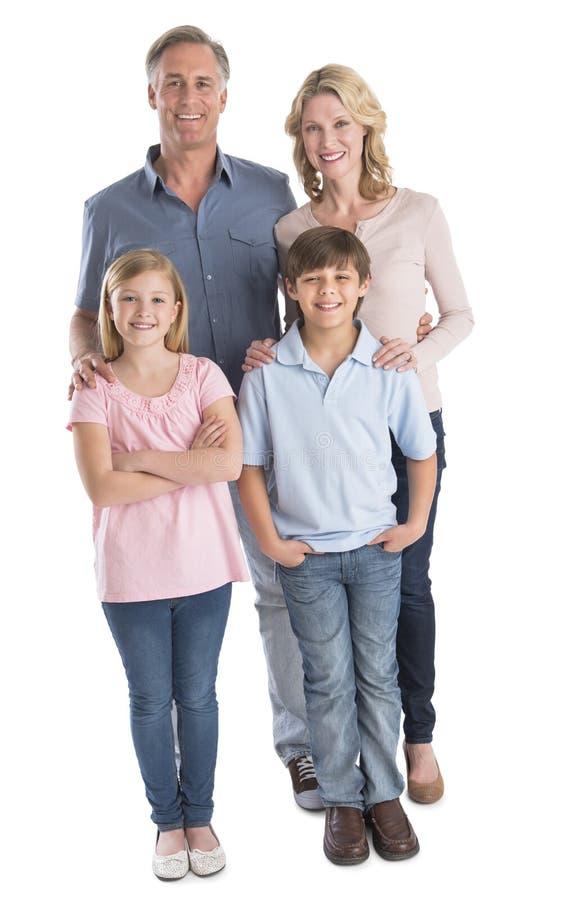 Família de quatro pessoas feliz que sorri contra o fundo branco foto de stock royalty free