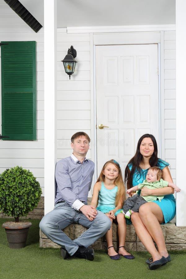 A família de quatro pessoas feliz senta no patamar de novo sua casa de campo. fotografia de stock