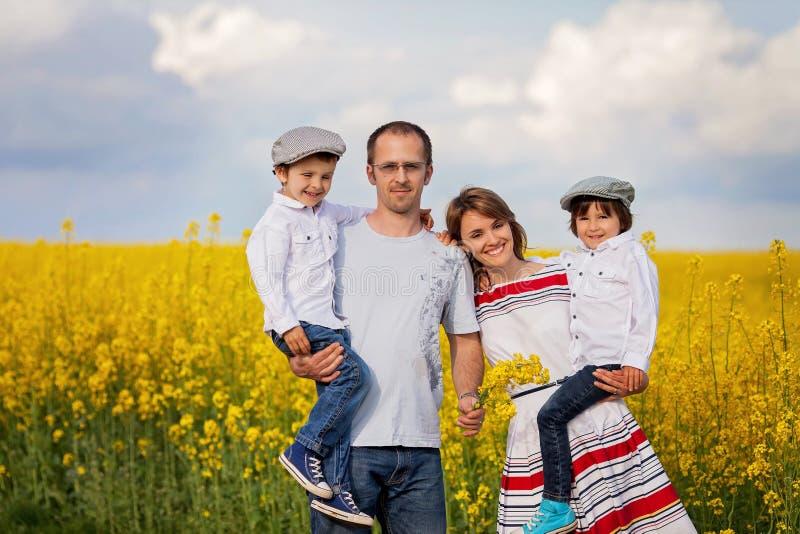 Família de quatro pessoas, mãe, pai e dois meninos, em uma violação de semente oleaginosa f foto de stock