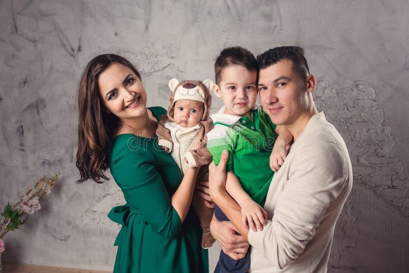 Família de quatro pessoas nova feliz no estúdio foto de stock royalty free