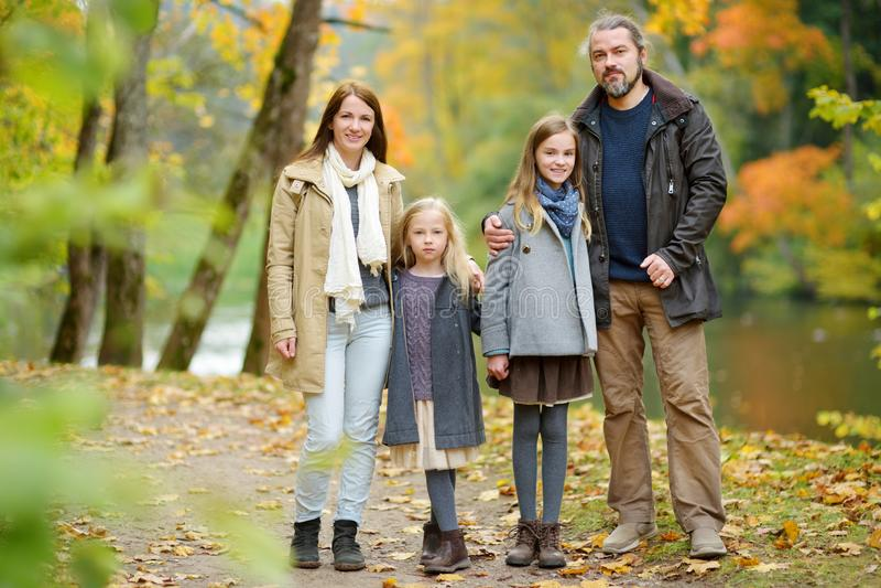 Família de quatro pessoas nova que tem o divertimento no parque do outono Pais e duas crianças que apreciam-se no dia morno da qu fotos de stock royalty free