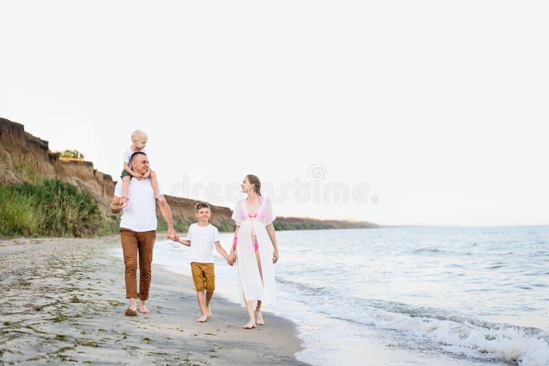 Família de quatro pessoas que anda ao longo do litoral pais e dois filhos Fam?lia amig?vel feliz fotografia de stock