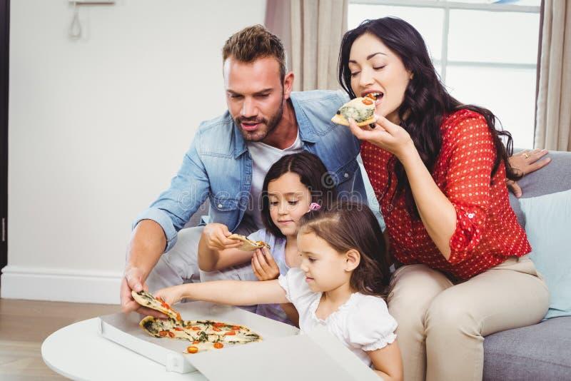 Família de quatro pessoas que come a pizza em casa fotografia de stock