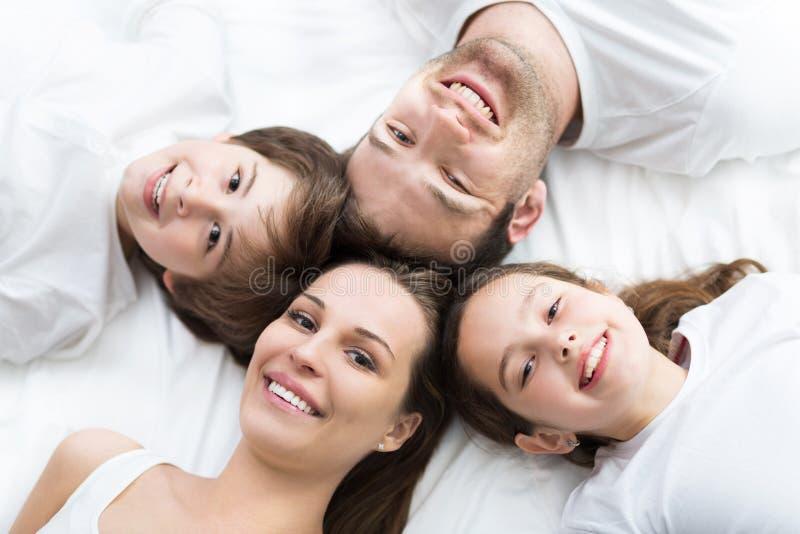 Família de quatro pessoas que encontra-se na cama fotos de stock