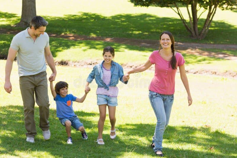 Família de quatro pessoas que guarda as mãos e que anda no parque imagens de stock
