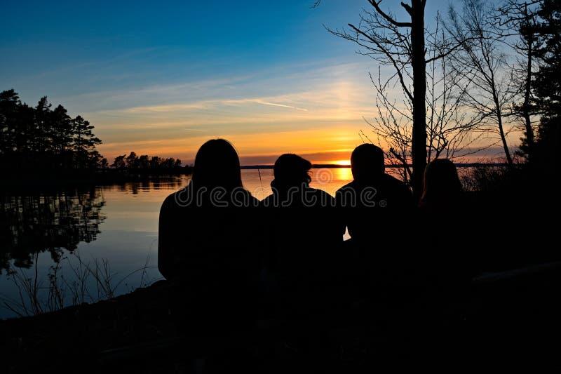 Família de quatro pessoas que olha o por do sol sobre um lago fotografia de stock