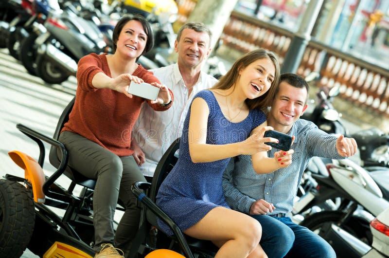 Família de quatro pessoas que senta-se na excursão grande elétrica foto de stock