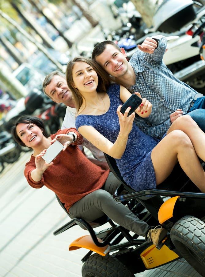 Família de quatro pessoas que senta-se na excursão grande elétrica imagem de stock