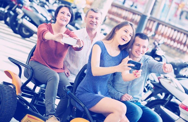 Família de quatro pessoas que senta-se na excursão grande elétrica imagens de stock royalty free