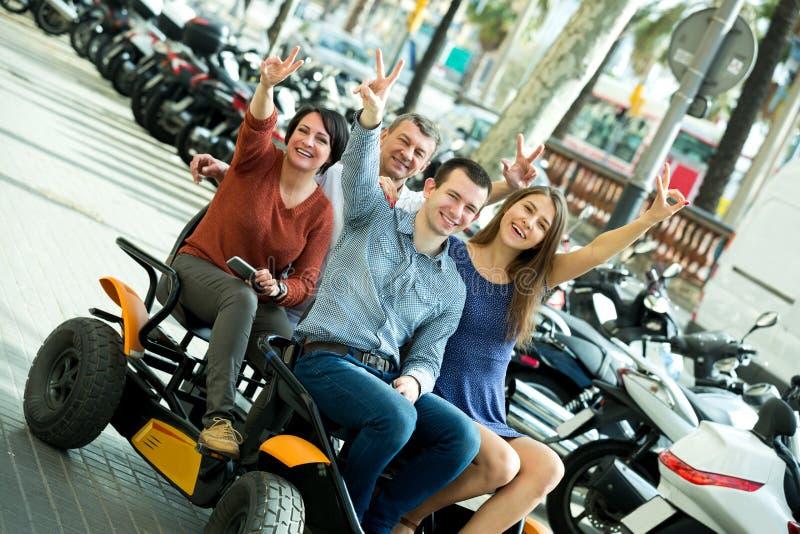 Família de quatro pessoas que senta-se na excursão grande elétrica imagem de stock royalty free