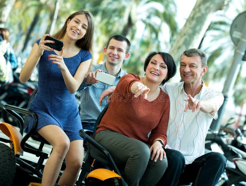 Família de quatro pessoas que senta-se na excursão grande elétrica fotografia de stock royalty free
