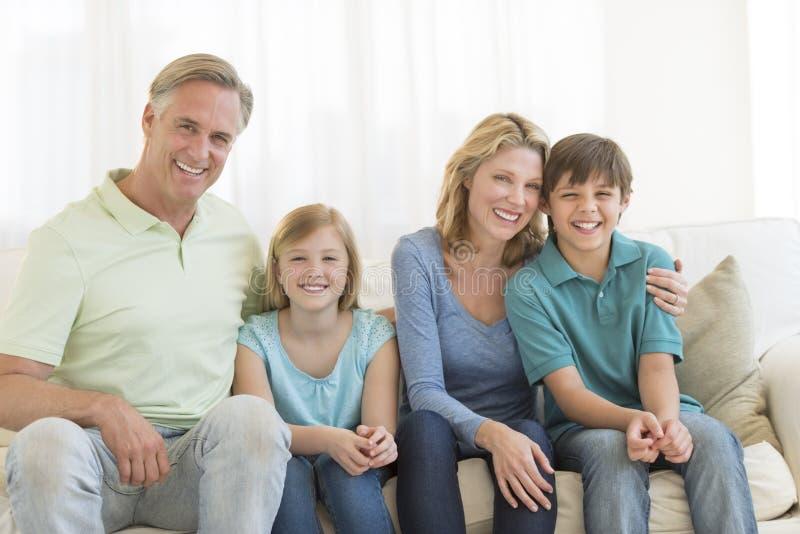 Família de quatro pessoas que sorri junto no sofá foto de stock royalty free