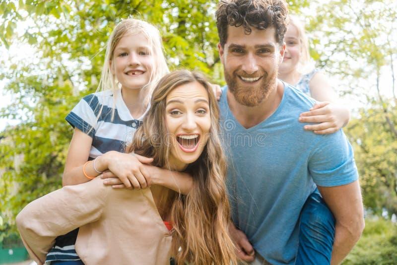 A família de quatro pessoas que tem o divertimento que leva as crianças reboca fotos de stock royalty free