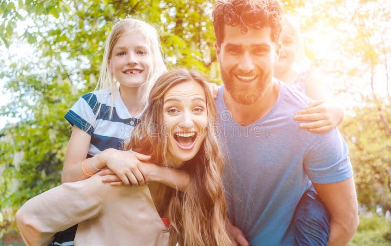 A família de quatro pessoas que tem o divertimento que leva as crianças reboca imagem de stock royalty free