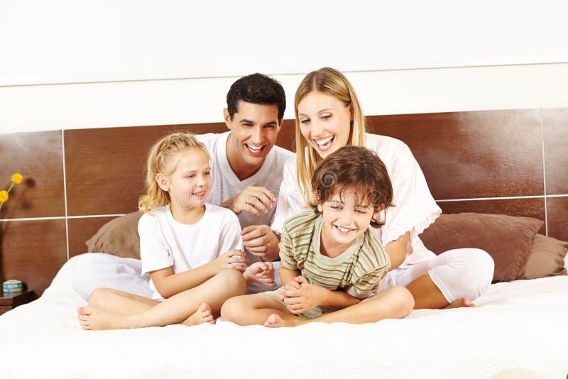A família de riso está sentando-se na cama fotografia de stock