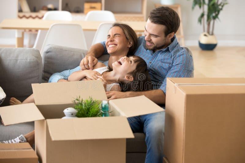 Família de riso para passar o tempo que tem o divertimento na casa nova fotografia de stock