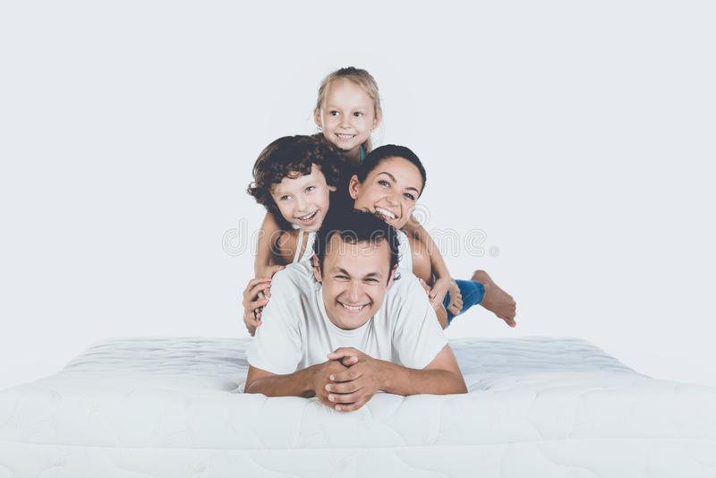 Família de sorriso bonito que encontra-se no colchão ortopédico foto de stock