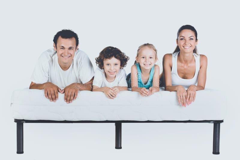 Família de sorriso bonito que encontra-se no colchão ortopédico imagens de stock