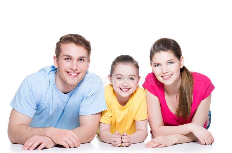 Família de sorriso com a criança que senta-se na camisa colorida imagens de stock royalty free