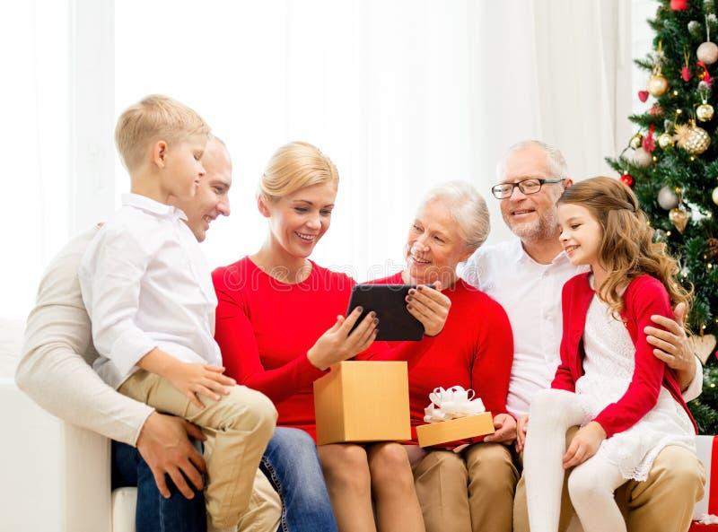 Família de sorriso com PC e caixa de presente da tabuleta em casa foto de stock