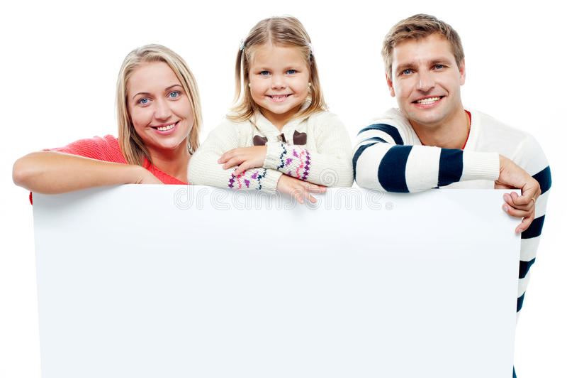 Família de sorriso com whiteboard em um estúdio imagens de stock