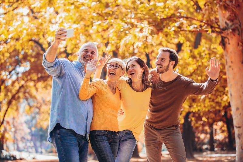 A família de sorriso em um dia dos outonos no parque faz o selfie imagens de stock
